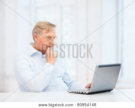 technology, oldness and lifestyle concept - old man in eyeglasses working with laptop computer at home