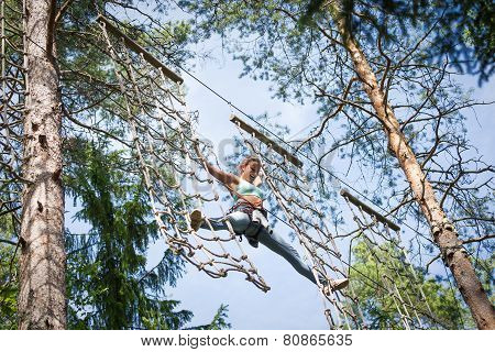 Young brave woman climbing in a adventure rope park