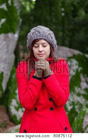 Young woman shivering with cold on a forest wearing a red overcoat, a beanie and gloves during winter