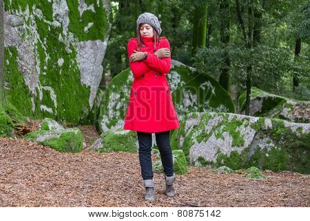 Young woman shivering with cold and embracing herself on a forest wearing a red overcoat, a beanie and gloves during winter