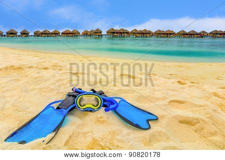 Snorkling Gear On The Beach With Water Bungalows And The Beach In Maldives