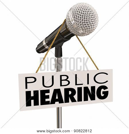 Public Hearing words on sign around a microphone to illustrate feedback, input, opinion or information sharing during a government or association meeting