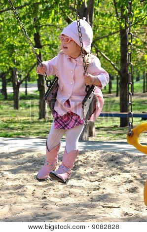 Cute toddler girl riding on swing at the children's playground