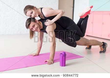 man doing push ups with woman laying on back at gym or home smiling looking at camera concept fitness sport training teamwork and lifestyle. poster