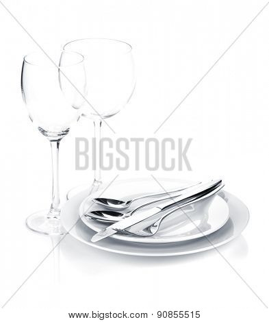 Silverware or flatware set over plates and wine glasses. Isolated on white background
