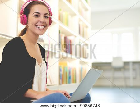 Young Woman Listening To Music As She Studies