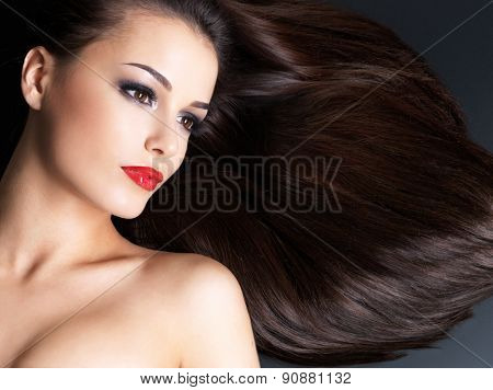 Young woman with long brown straight hairs on a dark background