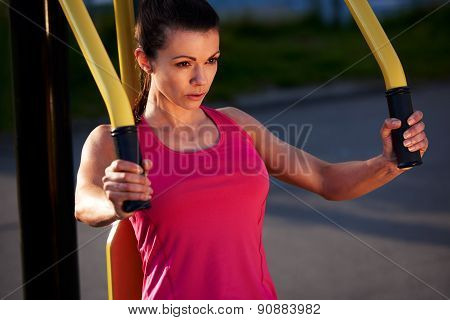 Woman Focussed While Exercising Upper Body.