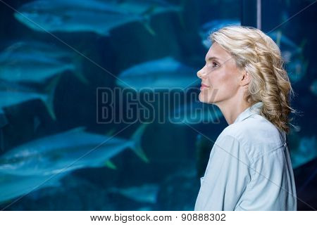 Pretty blonde looking at fish tank at the aquarium