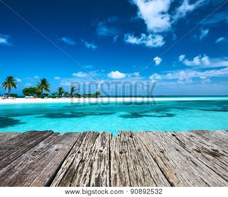 Beautiful beach with sandspit and old wooden pier at Maldives
