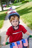 Boy riding his bicycle in a 4th of July neighborhood parade. poster