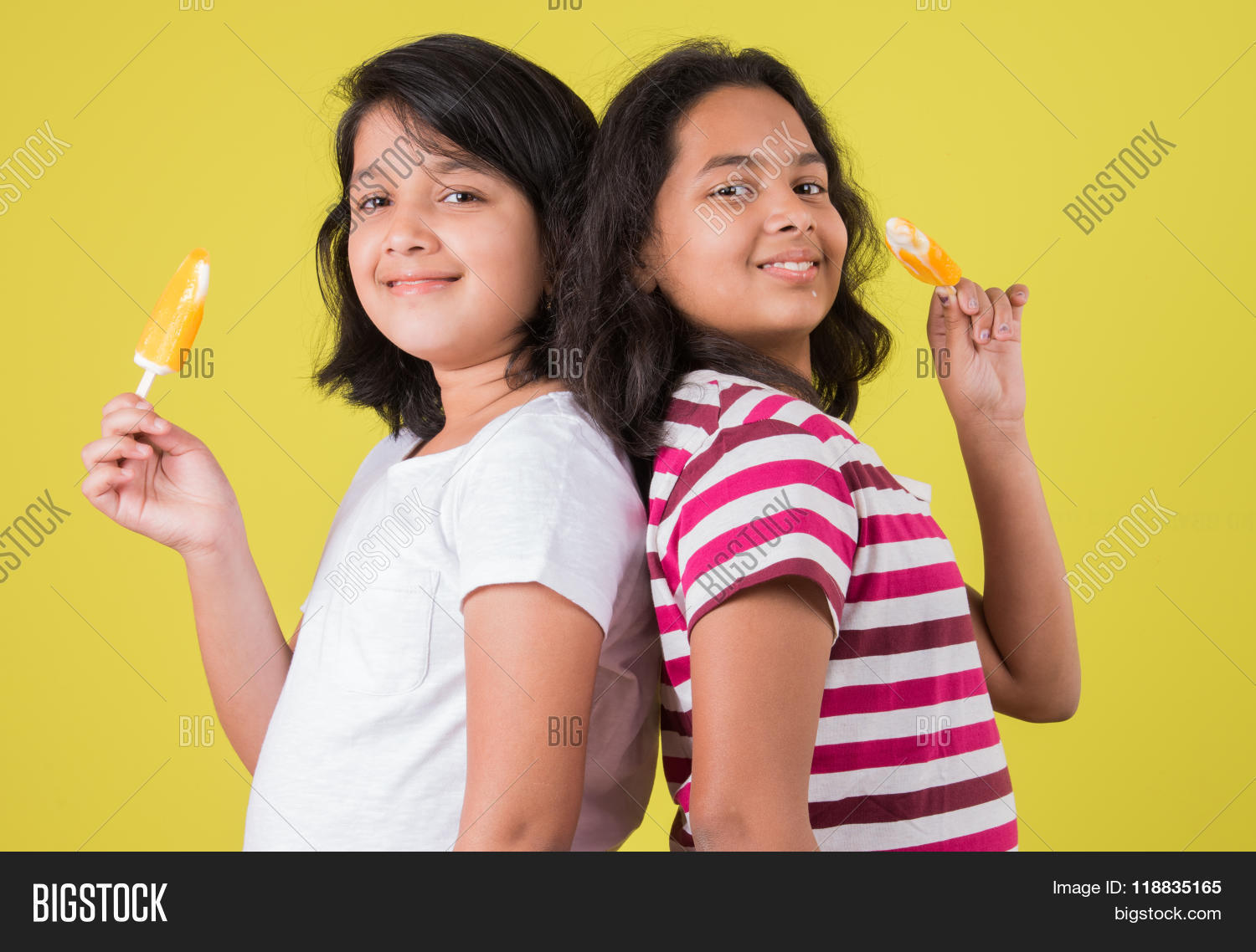 Two Indian Girls Eating Ice Cream Or Candy Asian Girl And