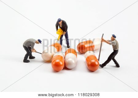 miniature people  - workers moving capsules pills