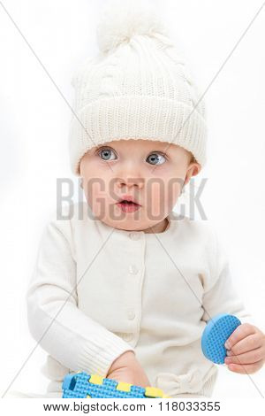 little child baby smiling playing with toy warm clothing hat isolated on white studio shot puzzle