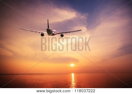 Airplane flying over amazing tropical ocean at sunset