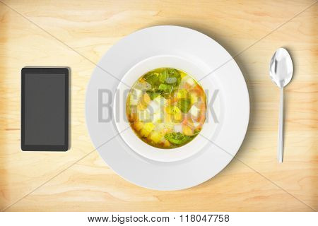 Minestrone Soup With Cell Phone And Sppon On Wooden Table