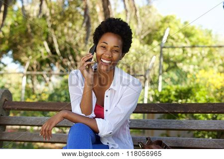 Relaxed African Woman Sitting On A Park Bench And Using Cell Phone