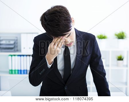 Young Businessman With Stress Rubbing His Eyes