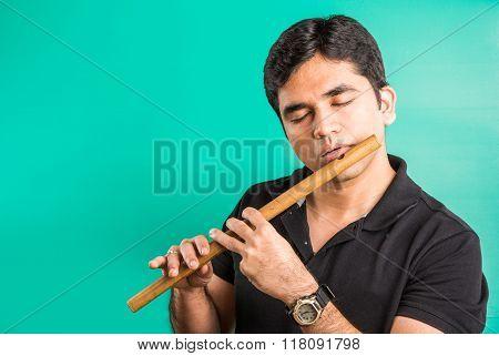 indian man playing flute, asian man playing flute, indian musician, indian man and flute, asian man