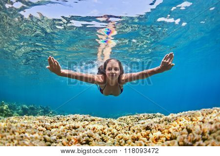 Young Woman Dive Underwater Over Coral Reef In Sea