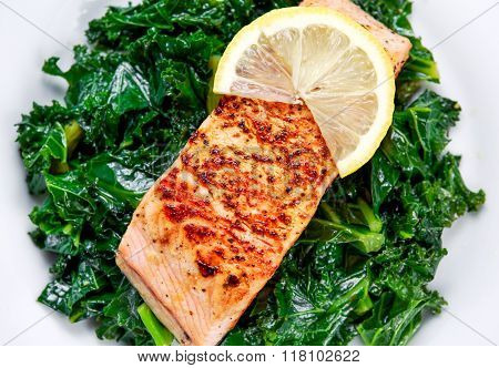 Pan fried Salmon Served with Kale on plate