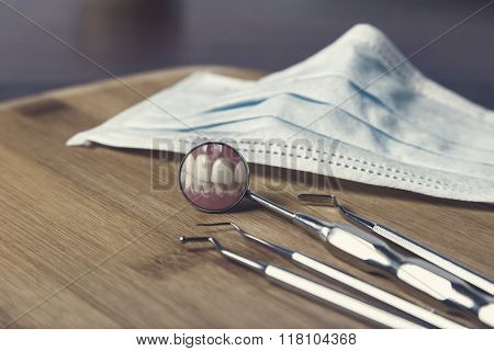 Dentists Tools And Mask With Reflection Of Teeth
