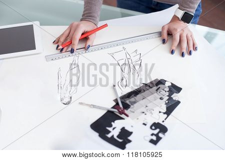 Cheerful female photo artist is working in office