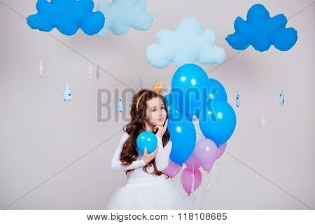 Cute little princess girl standing among balloons in room over white background. Looking at camera.