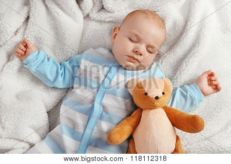 Adorable baby sleeping with teddy bears on sofa in the room, close up