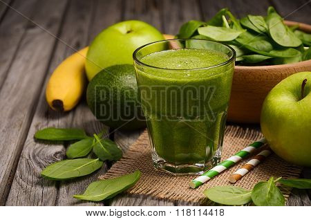 Green smoothie with apple, banana, avocado and spinach on a wooden rustic background.