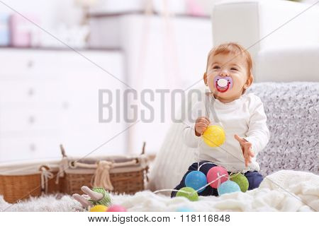 Sweet baby girl with a soother playing on a floor