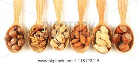 Wooden spoons with hazelnuts, walnuts, pistachios, almonds, acorns and peanuts, isolated on white