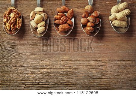 Walnut kernel, pistachios, almonds, hazelnuts and peanuts in the spoons on the wooden table