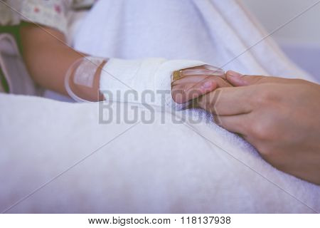 Close Up Hand Of Parent Holding Hand Of Child In Hospital. Retro Style.