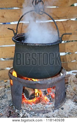 Big Black Pot With The Fire Lit And The Dense White Smoke