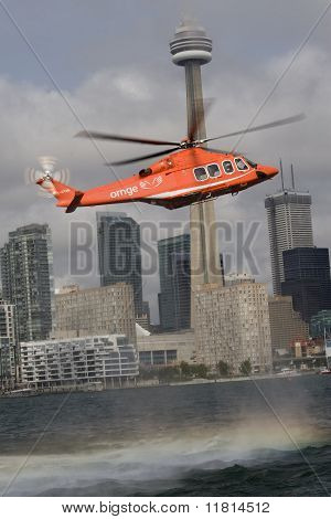 New AW139 helicopter hovers over the lake Ontario with downtown Toronto in the background