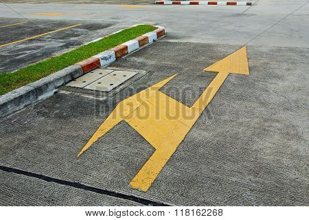 A yellow traffic arrow signage on an asphalt road indicating a detour left turn.