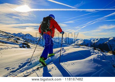 Ski tour - skier climbing to the top