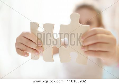 Child girl holding  two big wooden puzzle pieces. Hands connecting jigsaw puzzle. Close up photo wit
