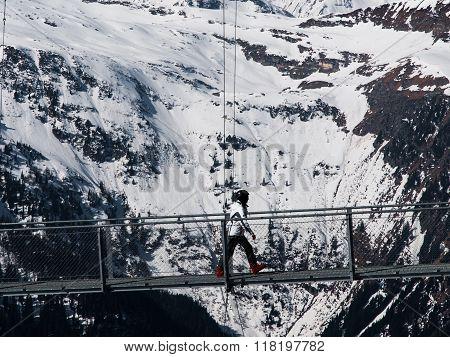 Skier walks on mountain suspension bridge