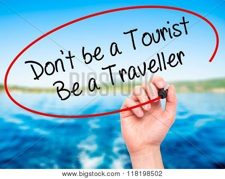 Man Hand Writing Don't Be A Tourist Be A Traveller  With Black Marker On Visual Screen