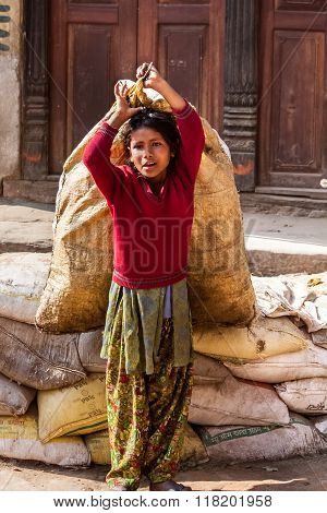 Bhaktapur, Nepal - April 19, 2013: Child Labour In Asia. Girl Teenager Drags The Heavy Bags.
