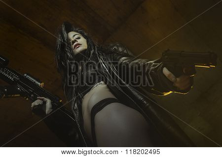 violence, brunette girl dressed in black leather with guns and pistols in a garage, scene of action