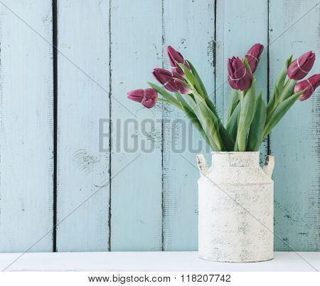 Bouquet of tulip flowers in vintage vase on the shelf over blue wooden background, shabby chic interior decor