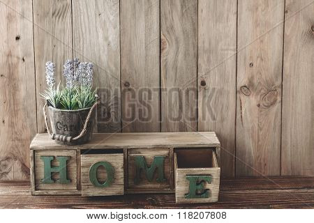 Storage box with Home letters and flowers in a pot on wooden background, home rustic decor, cottage living