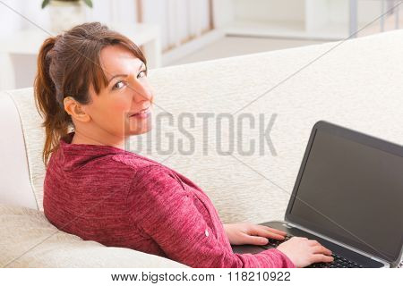 Deaf woman wearing hearing aid using laptop at home