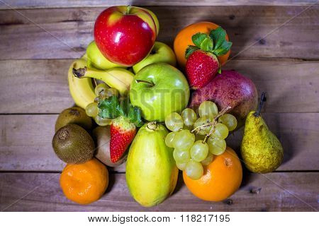 Mixed fresh fruits on old wooden background.