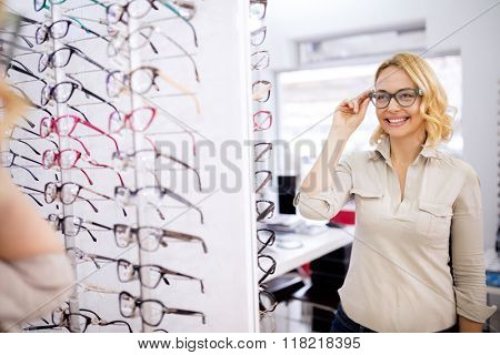 Pretty female try very nice frame for eyeglasses in optician shop