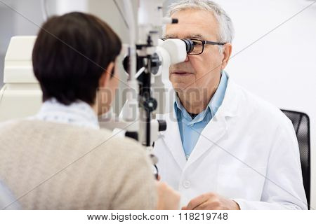Senior male eye specialist look in ophthalmoscope and perform eye review