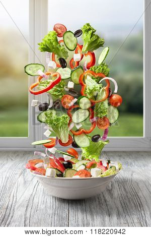 flying salad on wood against window with summer background. Greek salad: red tomatoes, pepper, cheese, lettuce, cucumber and olives
